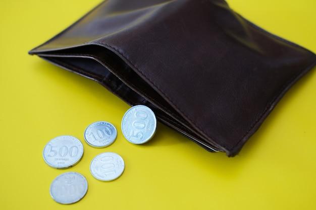 Monety rupii indonezyjskiej rozłożone z wnętrza portfela na żółtym tle