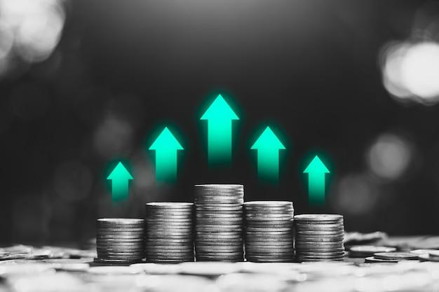 Monety są u góry z zielonymi ikonami technologii, koncepcjami wzrostu finansowego.