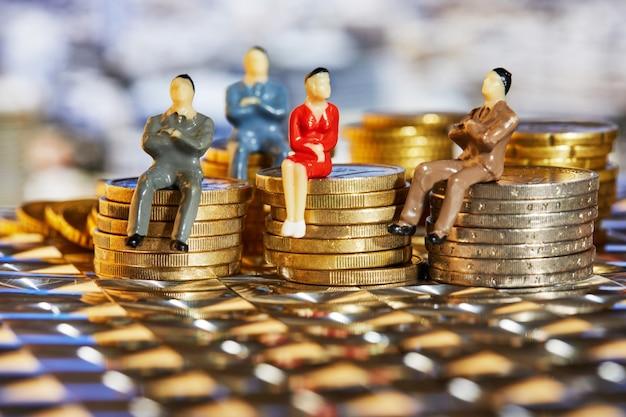 Monety są ułożone jedna na drugiej, a na nich siedzą ludzie biznesu, kryzys rynkowy i kruchy rynek.