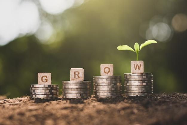 Monety są ułożone w stos z zielonymi ikonami technologii u góry, koncepcjami wzrostu finansowego.