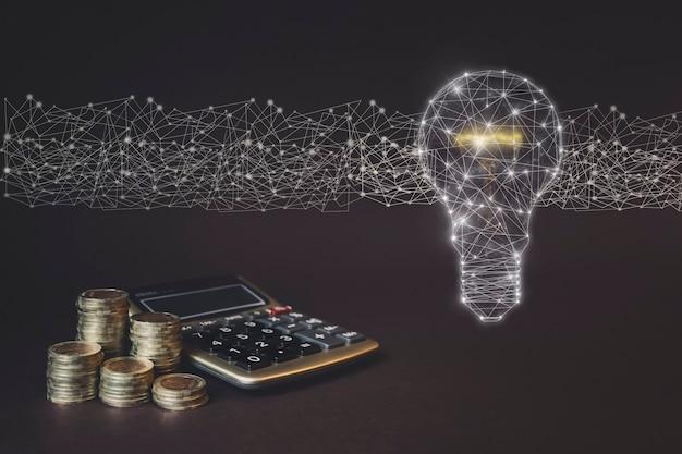 Monety stos i kalkulator oraz wirtualny gologram żarówek. koncepcja jasnego pomysłu na biznes pieniędzy