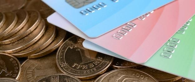 Monety ukraińskie pieniądze i kolorowe karty kredytowe z bliska