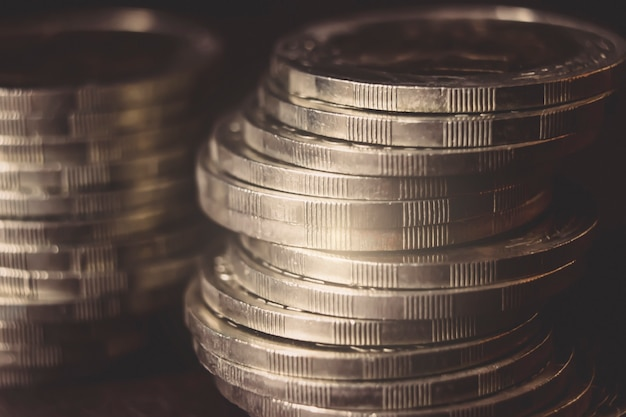 Monety ułożone jeden na drugim w różnych pozycjach na ciemnym tle. koncepcja pieniędzy. zbliżenie. koncepcja pieniędzy i oszczędności. sukces, bogactwo i ubóstwo, pojęcie ubóstwa. koncepcja rozwoju biznesu.
