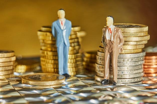 Monety ułożone jeden na drugim z postaciami ludzi biznesu