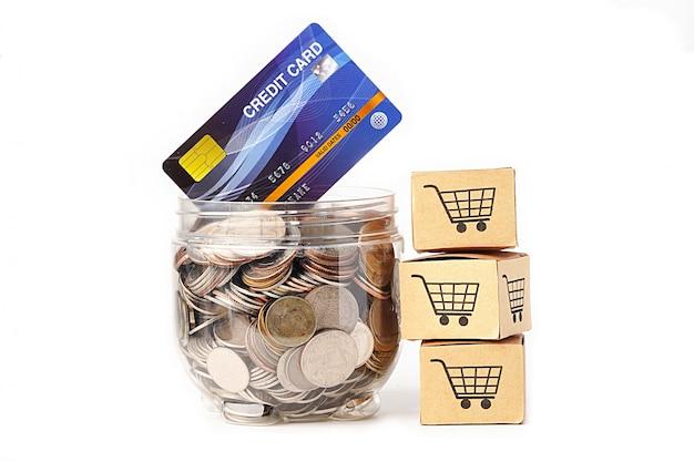 Monety w plastikowej butelce z modelem karty kredytowej i pudełkami na zakupy.