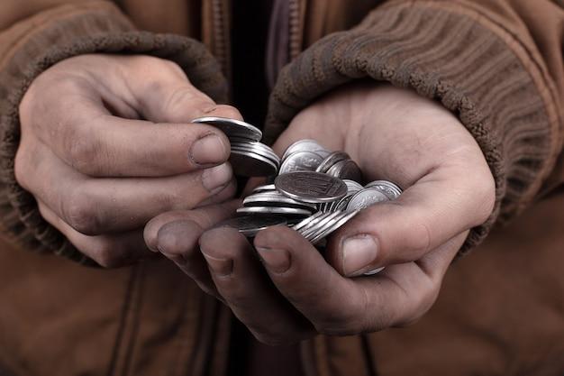 Monety w rękach żebraka, dobry człowiek daje jałmużnę biednym.