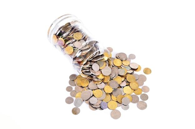 Monety w słoiku na białym tle