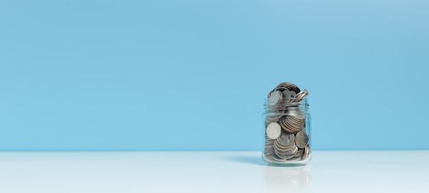 Monety w szklanej butelce umieścić na niebieskim tle tabeli, zapisać wzrost lub koncepcja inwestycji.