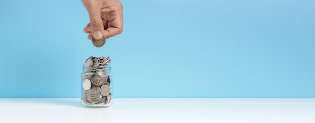 Monety w szklanej butelce umieścić na stole ręką oddanie monety niebieskie tło, wzrost zapisz lub koncepcja inwestycji.
