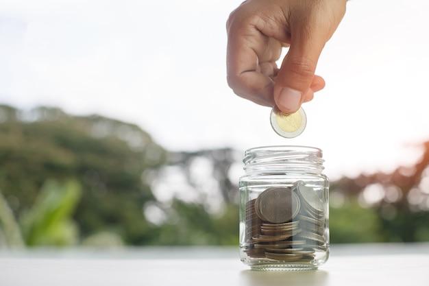 Monety w szklanej butelce umieścić na stole ręką oddanie pieniędzy monety natura tło, wzrost zapisać lub koncepcja inwestycji.