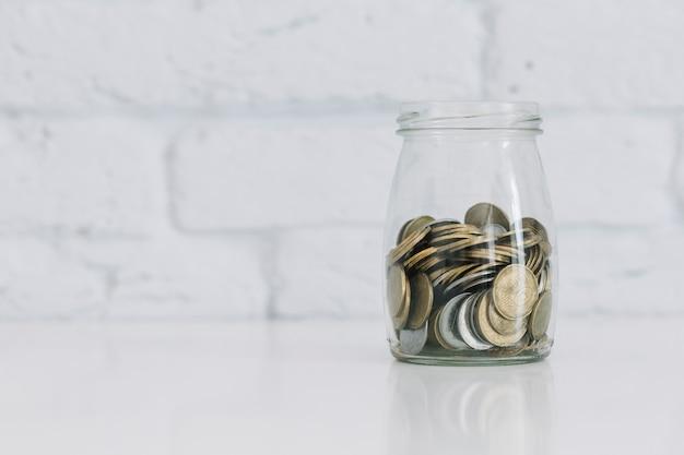 Monety w szklanym słoju na biurku przeciw białej ścianie