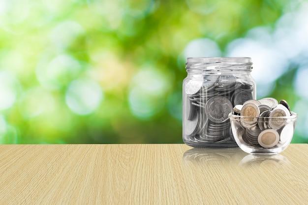 Monety w szklanym słoju na drewnianej podłodze, monety oszczędnościowe - koncepcja inwestycji i odsetek oszczędności koncepcja pieniędzy, rosnące pieniądze na skarbonce. pojedynczo na zielonym tle