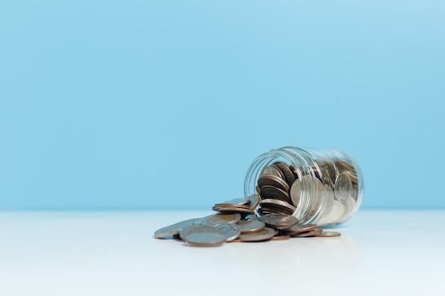 Monety wylane ze szkła słoika na niebieskim tle tabeli, oszczędzając na przyszłość, koncepcja biznesowa inwestycji.