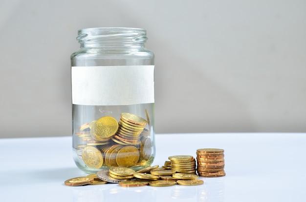 Monety wysypujące się ze szklanej butelki