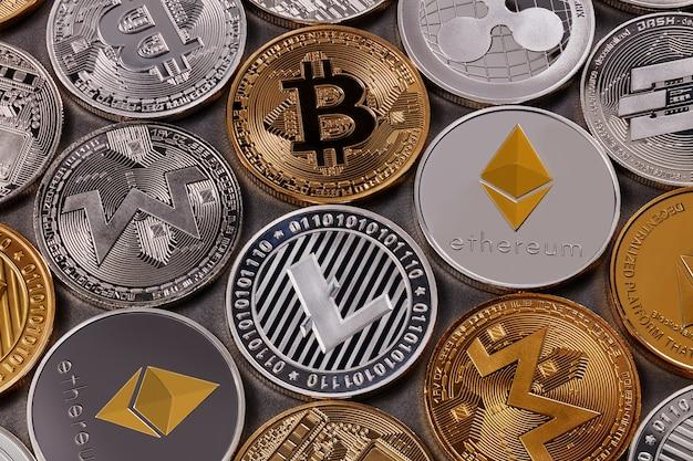 Monety złote i srebrne, ltc, eth, btc, xmr, xrp. wzór z różnych monet wirtualnej waluty na ciemnym tle. koncepcja kryptowalut i blockchain. widok z góry