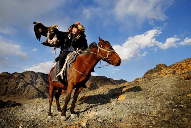 Mongolski mężczyzna na koniu z orłem