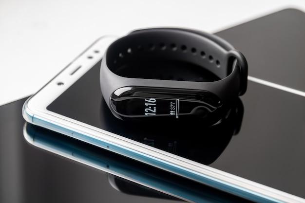 Monitor aktywności leży na smartfonie i tablecie na białym tle
