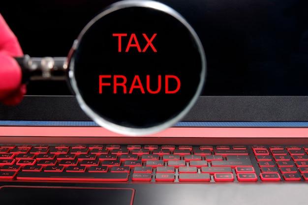 Monitor komputera z czerwonym tekstem oszustwa podatkowe przez lupę.