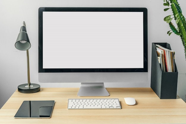 Monitor komputerowy z białym ekranem makiety na stole w biurze z materiałami eksploatacyjnymi
