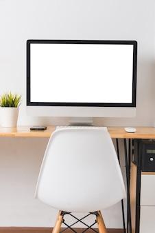 Monitor komputerowy z białym pustym ekranem na biurku biznesowym z bezprzewodową myszą, klawiaturą