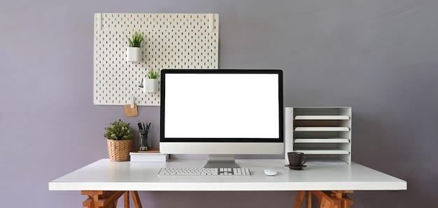 Monitor komputerowy z białym pustym ekranem umieszczonym na białym biurku i otoczony półką na książki