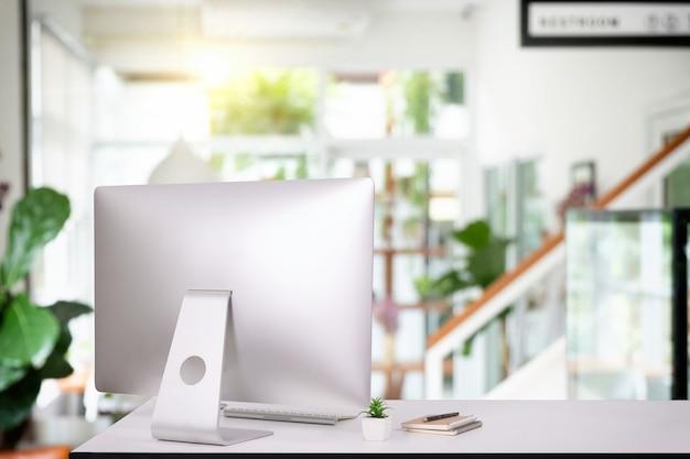 Monitor laptopa cyfrowe biurko pc klawiatura obszaru roboczego, pusty ekran filiżanka kawy na stole w jasnym wnętrzu pokoju biurowego, stylowy obszar roboczy z komputerem stacjonarnym, artykułami biurowymi, rośliną doniczkową i książkami