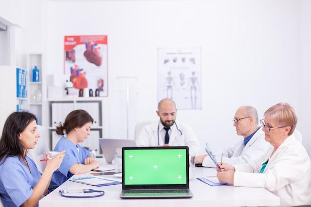Monitor laptopa z zielonym ekranem w konferencji w szpitalu. ekspert kliniczny terapeuta rozmawiający z kolegami o chorobie, specjalista od medycyny.