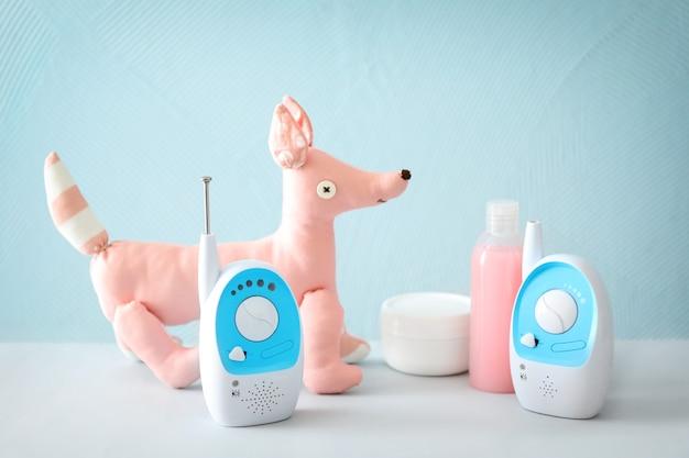 Monitory, zabawki i kosmetyki na stole na tle koloru