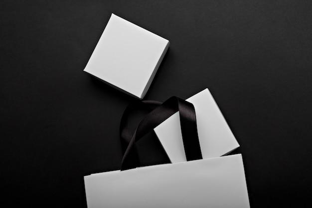 Monochromatyczna fotografia biała papierowa torba i pudełka na czarnym tle. miejsce na logo twojej marki