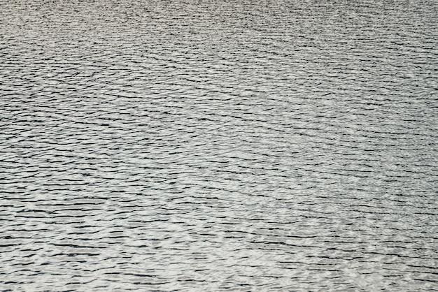 Monochromatyczne tekstury srebrna spokojna woda jeziora. medytacyjne fale na powierzchni wody. natura minimalne tło szarego jeziora. naturalne czarne białe tło z czystą wodą. fragment jeziora w skali szarości.