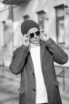 Monochromatyczny portret modnego, stylowego młodego atrakcyjnego hipster mężczyzny w okularach przeciwsłonecznych, na sobie płaszcz