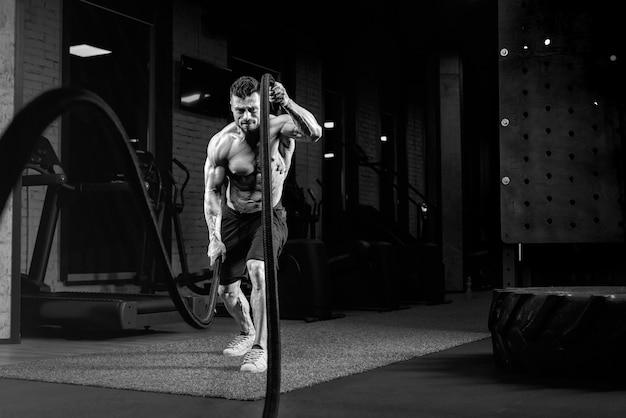 Monochromatyczny portret muskularny mężczyzna bez koszuli robi trening liny bojowej w siłowni.