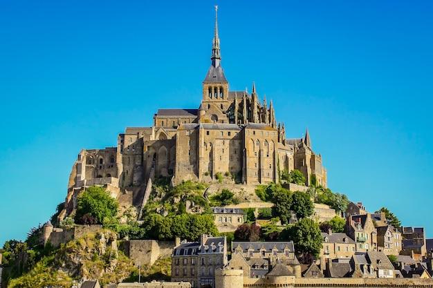 Mont saint michel ze spektakularnymi murami domów i klasztorem na szczycie