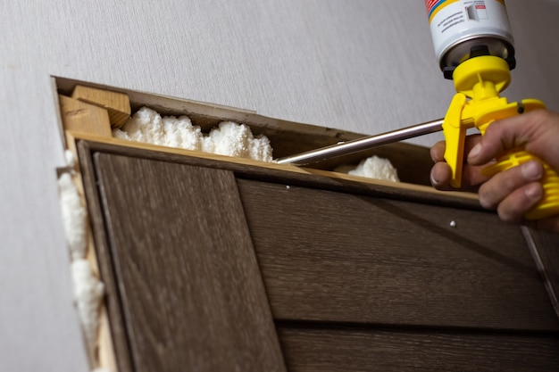 Montaż drzwi w domu. master spienia szczeliny między drzwiami a ścianą pianką poliuretanową.