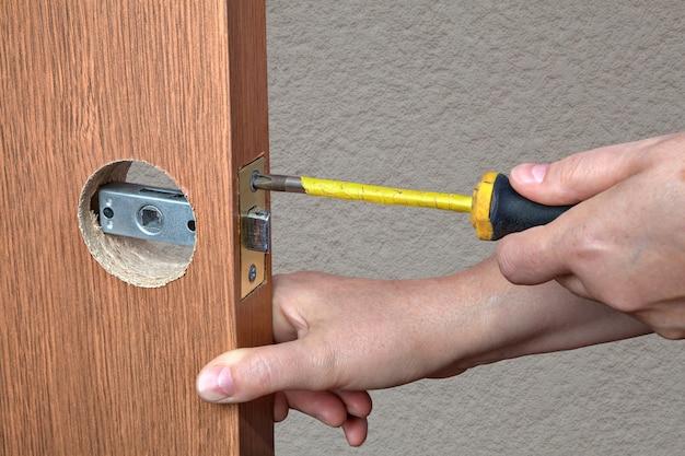 Montaż klamki z zatrzaskiem w drzwiach wewnętrznych, zbliżenie rąk instalatora ze śrubokrętem.