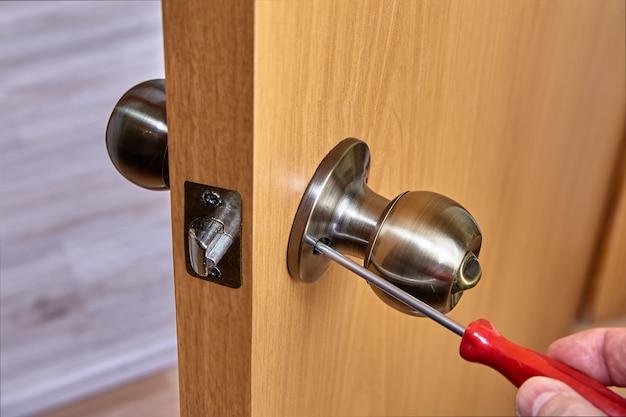 Montaż kulistych klamek w kolorze brązu w nowych drzwiach wewnętrznych
