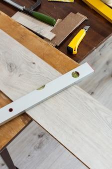Montaż laminatu lub parkietu w pokoju, pracownik montaż drewnianych podłóg laminowanych, zaznaczenie długości laminatu