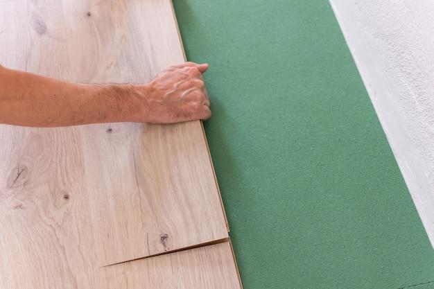 Montaż laminatu lub parkietu w pomieszczeniu, pracownik montujący drewnianą podłogę laminowaną, przyjazne dla środowiska arkusze dźwiękochłonne