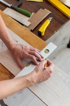 Montaż laminatu lub parkietu w pomieszczeniu, pracownik montujący drewnianą podłogę laminowaną, zaznaczając długość laminatu