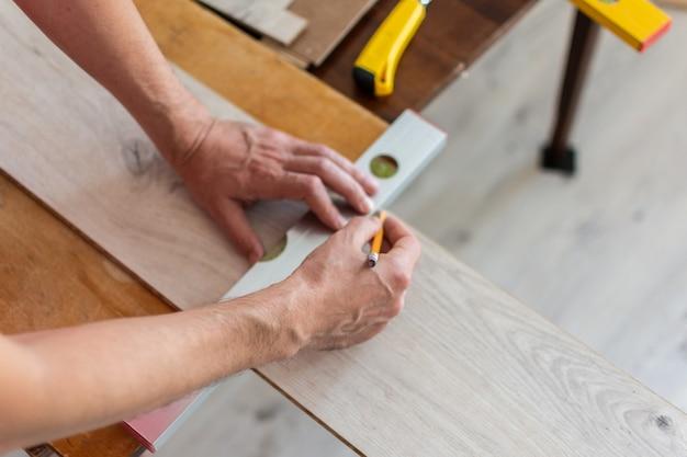 Montaż laminatu lub parkietu w pomieszczeniu, pracownik montujący podłogę z laminatu drewnianego, zaznaczanie długości laminatu