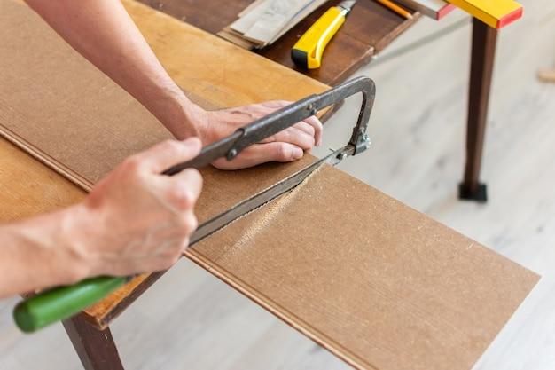 Montaż laminatu lub parkietu w pomieszczeniu, pracownik wycina piłą laminat o określonej długości