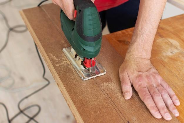Montaż laminatu lub parkietu w pomieszczeniu, pracownik wycina za pomocą wyrzynarki laminat o określonej długości
