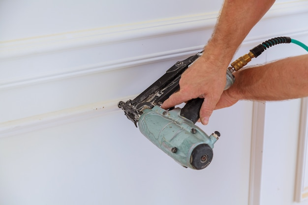 Montaż listew na ścianie odnowionego pomieszczenia.