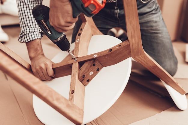Montaż mebli człowiek naprawa krzesła człowiek zbiera krzesło monter mebli z wiertarką kobieta na so