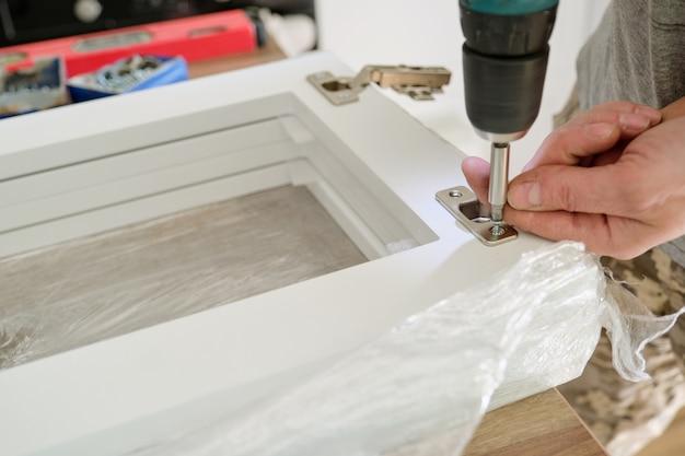 Montaż mebli, dokładne przykręcenie chromowanych zawiasów drzwi za pomocą profesjonalnych narzędzi
