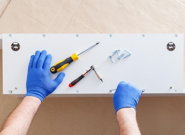 Montaż mebli. męskie dłonie w rękawiczkach mistrz zbiera meble za pomocą narzędzi śrubokręt, instrument w domu. przeprowadzki, majsterkowanie, naprawa i renowacja mebli. widok z góry.