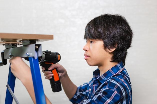 Montaż mebli. mężczyzna trzyma wiertarkę elektryczną do montażu mebli, rzemieślnik z wiertarką w śrubokręcie elektrycznym!
