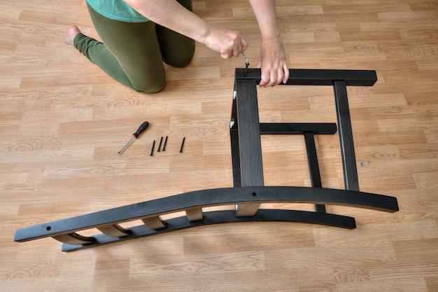 Montaż mebli z drewna, kobieta składająca drewniane elementy krzesła za pomocą wkrętu meblowego i klucza imbusowego.