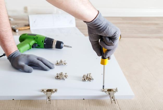 Montaż mebli za pomocą śrubokręta. męskie dłonie w szarych rękawiczkach mistrz zbiera meble za pomocą narzędzi śrubokręt, instrument w domu. przeprowadzki, majsterkowanie, naprawa i renowacja mebli.