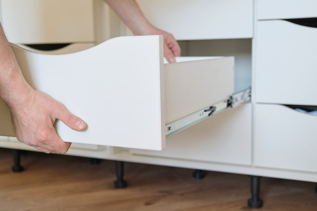 Montaż mebli. zbliżenie pracowników szczegóły dłoni i mebli